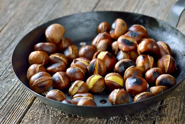 Heie herbstliche Maronen in der gelochten Kastanienpfanne auf rustikalem Holztisch serviert